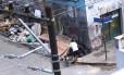 Com ajuda de um carrinho de mão, homem despeja lixo em calçada de esquina em Botafogo