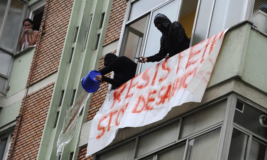 """Ativistas do """"Stop Deshaucios"""" jogaram água da varanda do prédio para tentar impedir a entrada dos policiais durante o despejo forçado em Oviedo ELOY ALONSO / REUTERS"""