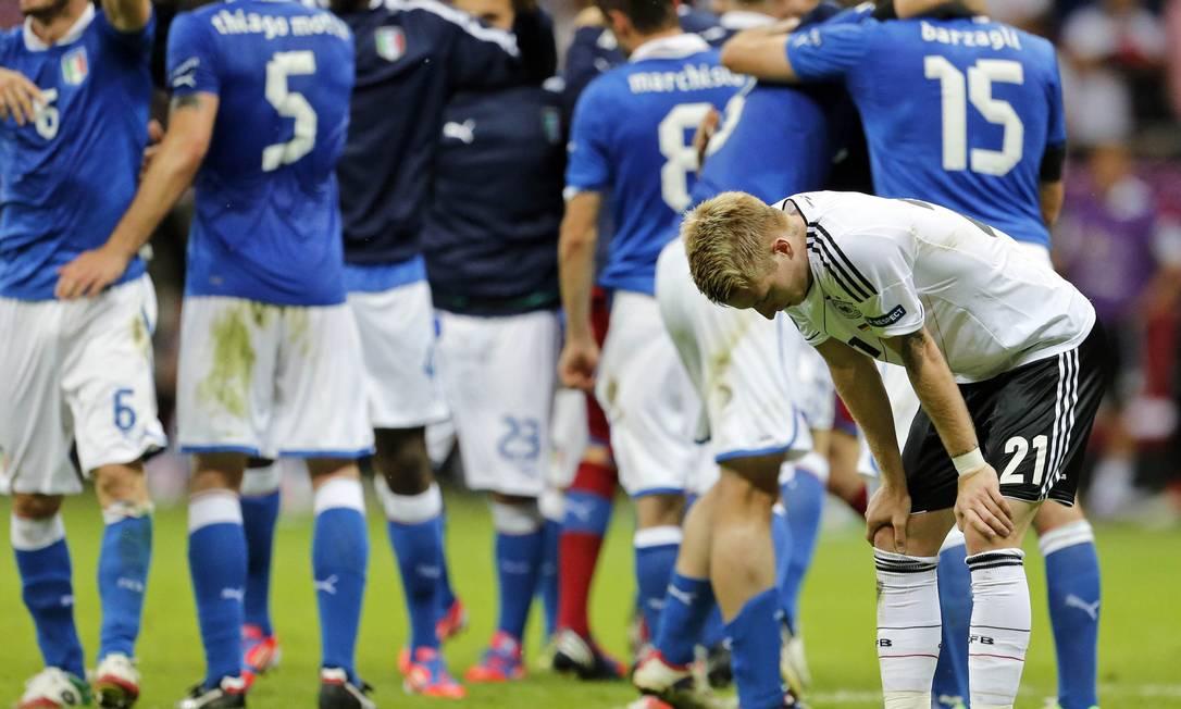 O jogador alemão lamenta a derrota enquanto, ao fundo, italiano celebram AP
