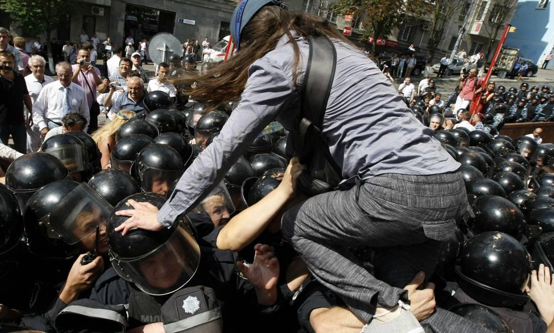 Manifestante escala barreira de policiais em Kiev ANATOLII STEPANOV / REUTERS