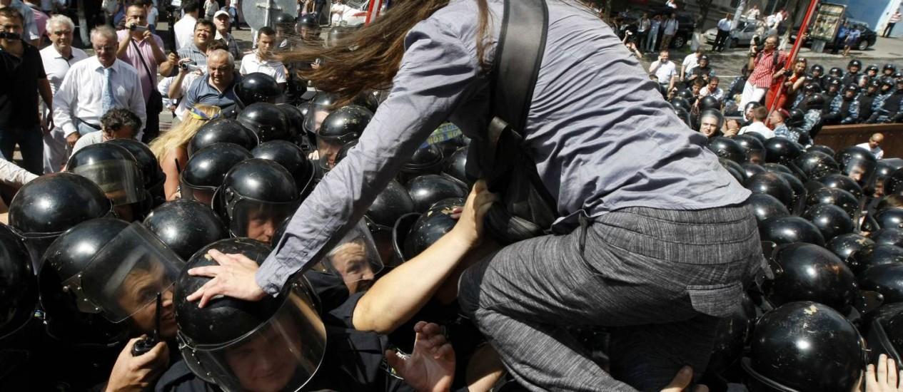 Manifestante escala barreira de policiais em Kiev Foto: ANATOLII STEPANOV / REUTERS