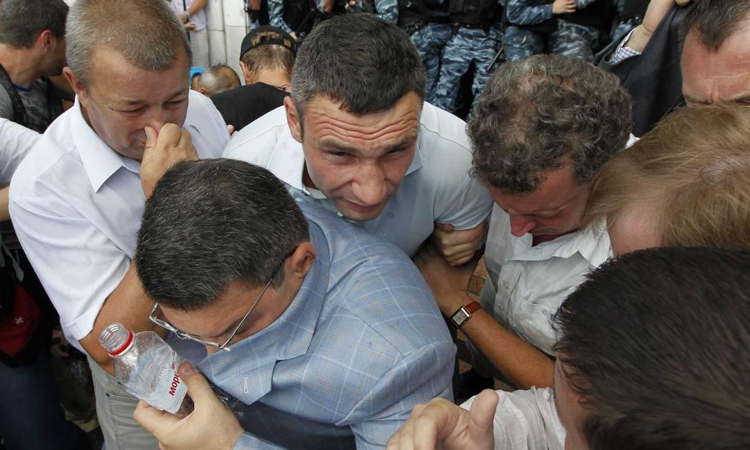 Vitali Klitschko (ao centro), ex-campeão de box e político, tenta escapar do spray de pimenta usado pela polícia, em Kiev Reuters