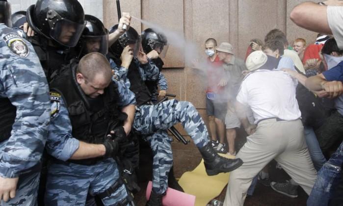 Policiais usam spray de pimenta contra manifestantes, diante do prédio da Câmara, em Kiev