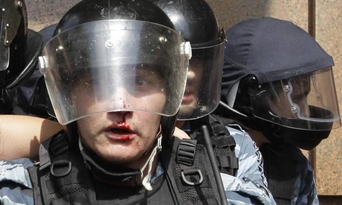 Um policial ferido após o confronto com manifestantes AP