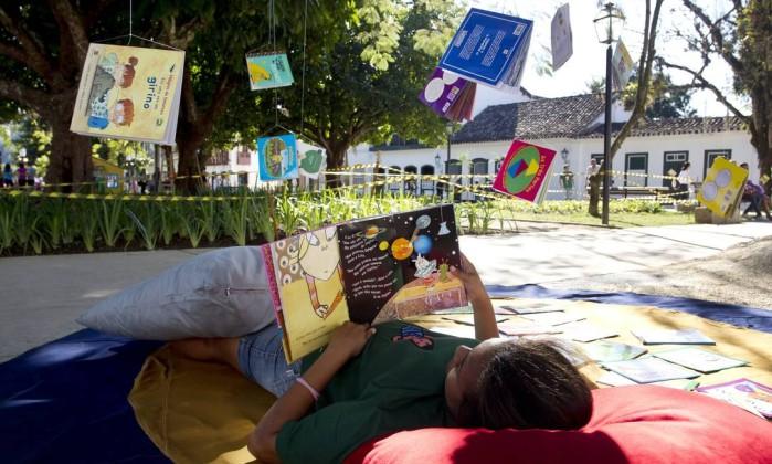 Criança aproveita o sol e a estrutura da Flip para ler na praça Márcia Foletto / Agência O Globo