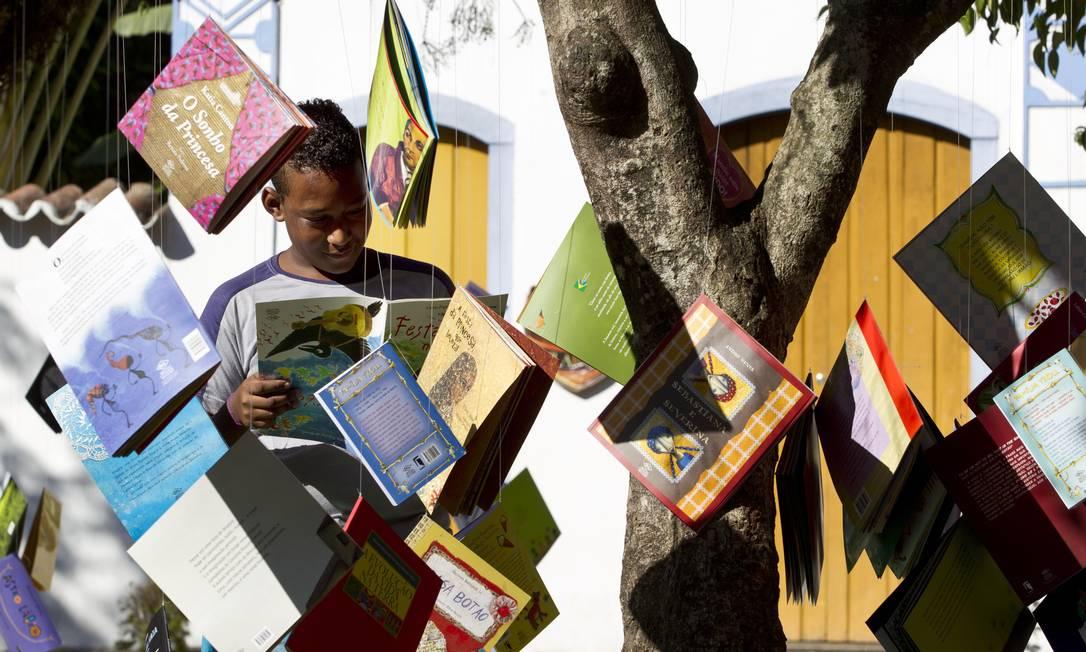 Criança lê um dos livros pendurados na árvore da praça Márcia Foletto / Agência O Globo