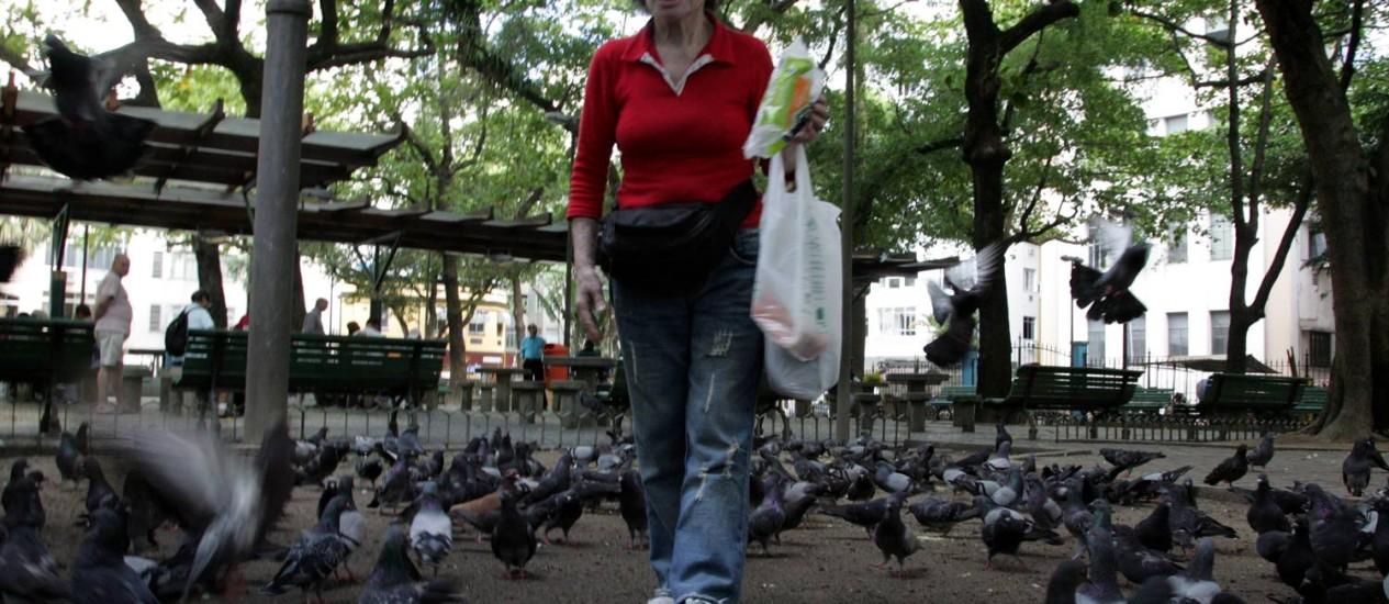 Dália Shafran alimenta os pombos na Serzedelo Correia: em meio ao movimento, sossego na área interna da praça Foto: Pedro Teixeira / Agência O Globo