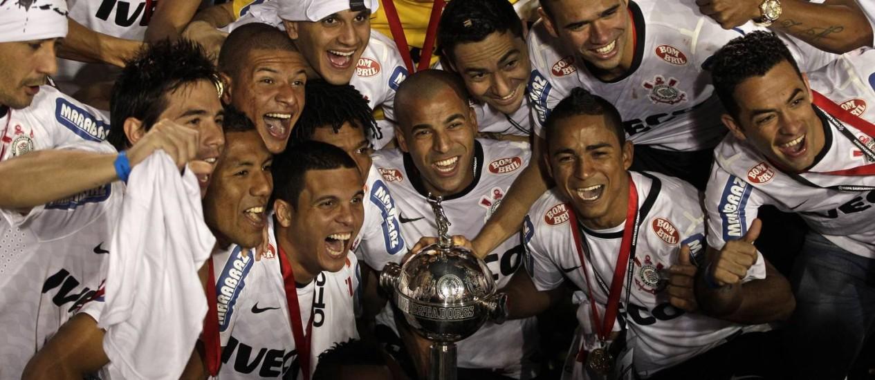 Emerson (ao centro) e os demais jogadores do Corinthians posam ao lado da Taça Libertadores Foto: Victor R. Caivano / AP