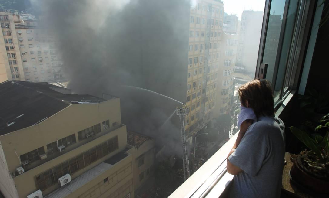 Em prédio vizinho, pessoa observa incêndio na Avenida Nossa Senhora de Copacabana Custodio Coimbra / O Globo