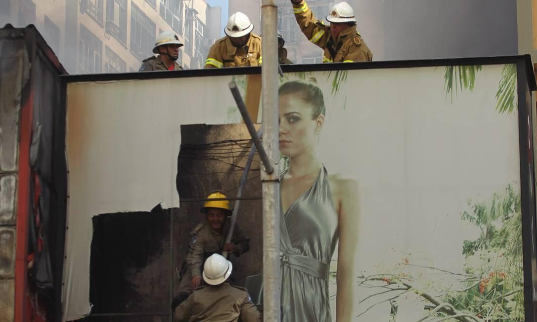 Bombeiros trabalham na loja de roupas também atingida pelo fogo Custodio Coimbra / O Globo