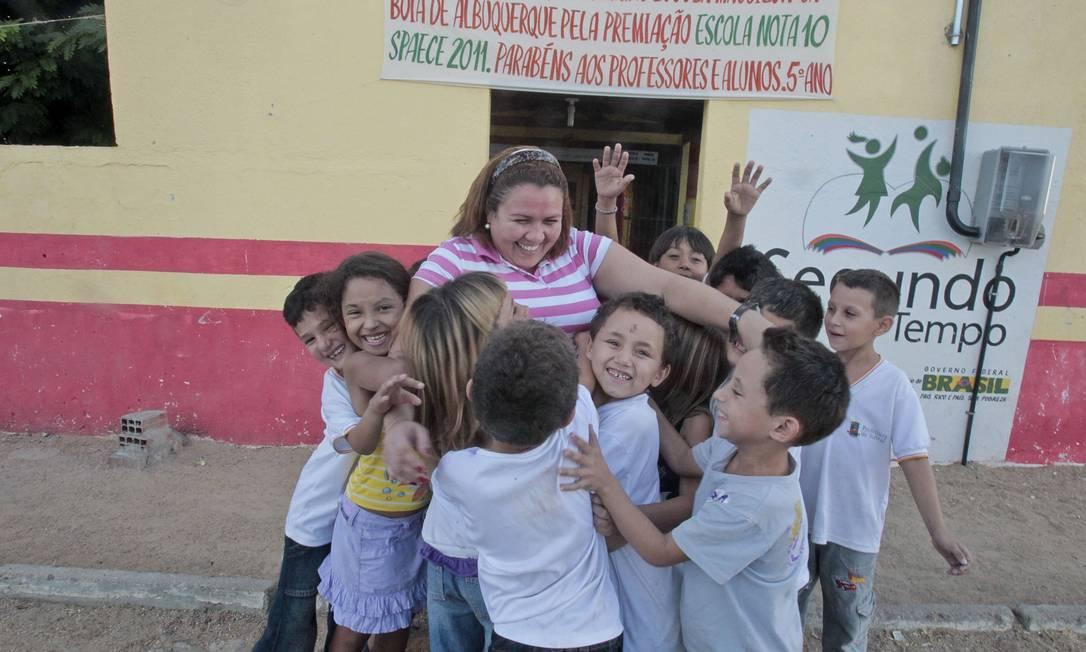 MÁRCIA DE Souza, diretora da escola Massilon, é abraçada por alunos: sem defasagem idade-série Foto: Agência O Globo / Jarbas Oliveira