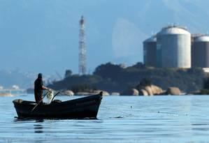 Pescador joga a rede a poucos metros de um terminal de gás na Baía de Guanabara: disputa por áreas de pesca estaria por trás da violência Foto: Custódio Coimbra / O Globo