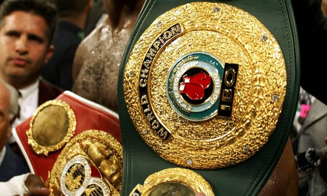 Lennox Lewis após derrotar Mike Tyson, abraçado ao cinturão de campeão mundial, em 2002 Arquivo / Reuters