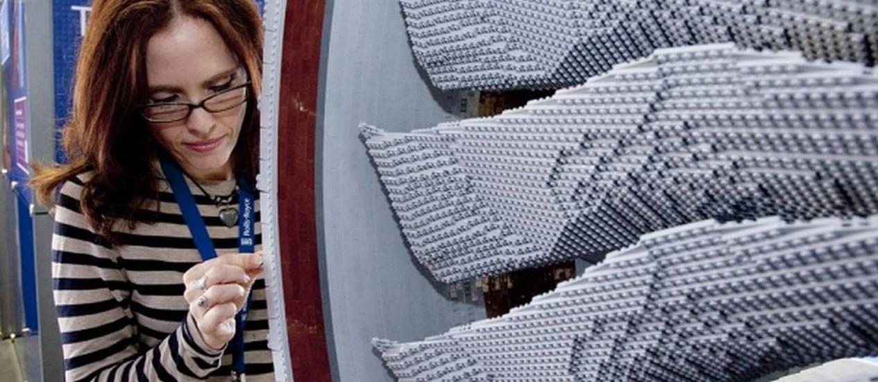 Funcionária da Rolls Royce meticulosamente ajusta uma das mais de 150 mil peças de Lego no modelo Foto: Reproduçao
