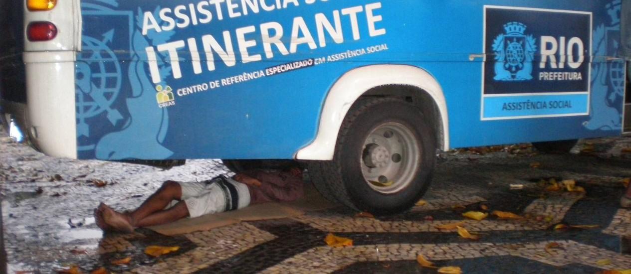 Na Central do Brasil, morador de rua dorme embaixo de ônibus da Secretaria Municipal de Assistência Social Foto: Foto do leitor Valnei Brunetto / Eu-repórter