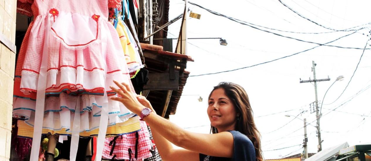 Moradora do Recreio, Sylvia Magalhães escolhe roupas infantis no Terreirão Foto: Bia Guedes / Agência O Globo