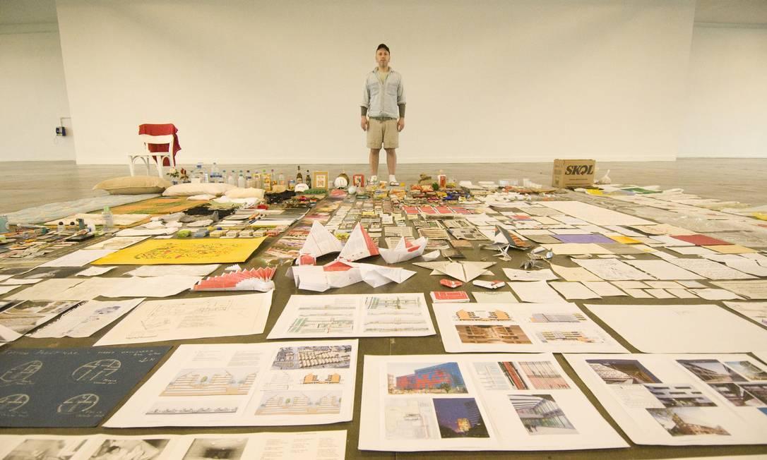 """Maurício Ianês na performance """"A bondade de estranhos"""", na Bienal de 2008. O artista começou a mostra nu e recebia doações dos visitantes. Na foto, já vestido com roupas que recebeu dos espectadores, ele posa com todas as doações recebidas ao longo da exposição Divulgação"""
