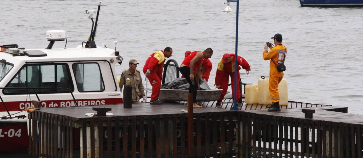 Bombeiros retiram do mar o corpo de copiloto de bimotor que caiu na quinta-feira, em Angra dos Reis Foto: Marcos Tristão / O Globo