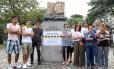 Manifestantes da UFRJ de braços cruzados ao lado do busto dos Imrãos Bernardelli, no Lido, que foram coberto com papel craft desenhados de carinhas tristes: cobrança por negociação