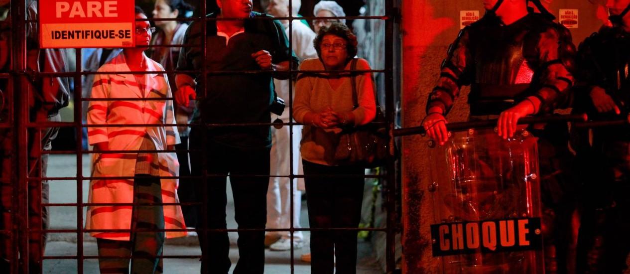 Agente do Batalhão de Choque aguarda, na sede do Iaserj, a transferência dos pacientes, iniciada no fim da noite de sábado Foto: Pedro Kirilos / Agência O Globo