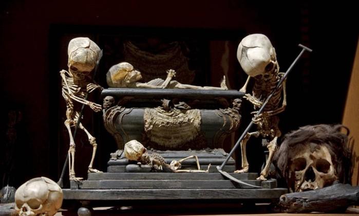 The Morbid Anatomy Library (Brooklyn, Nova York, EUA). Essa coleção privada tem velhos livros de medicina, modelos anatômicos em cera hiperrealistas, crânios e miudezes diversas. A escultura 'Memento mori' usa crânios e esqueletos de crianças Divulgação