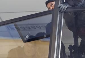 Policial do Bope, que ocupou a favela Nova Brasília, no Complexo do Alemão, examina um buraco de bala em janela da sede da UPP atacada Foto: Márcia Foletto / O Globo