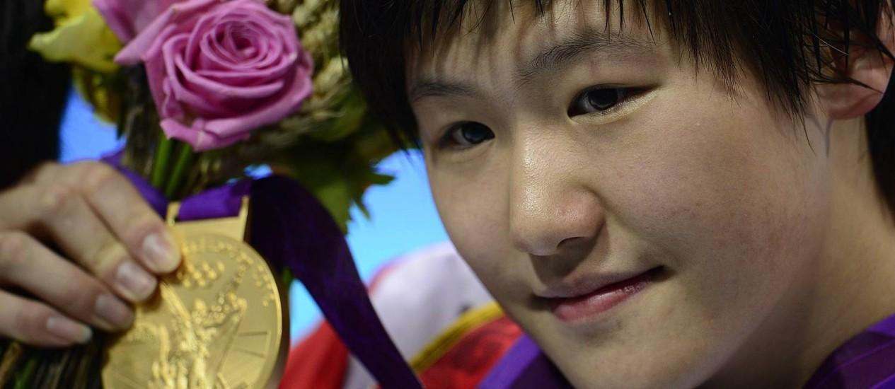 Ye Shiwen mostra com orgulho a medalha de ouro que ganhou Foto: Sean Kilpatrick / AP