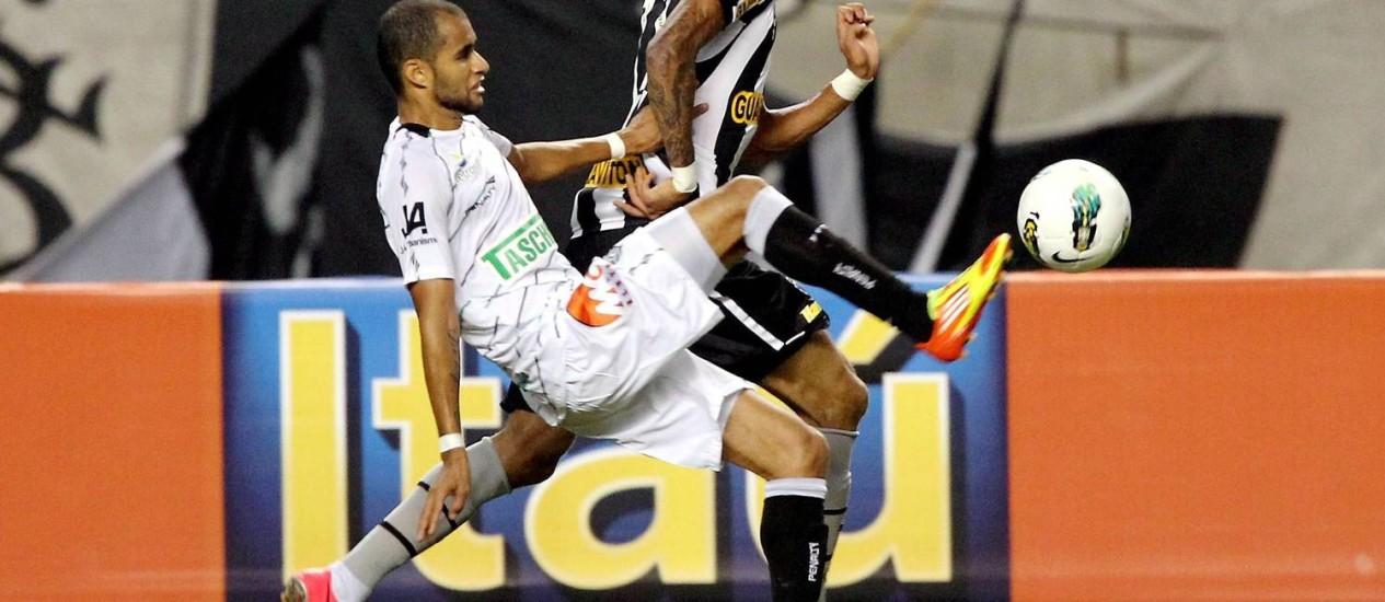 Rafael Marques disputa bola na partida contra o Figueirense Foto: Cezar Loureiro / O Globo