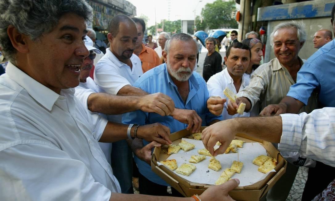 Deputado federal Chico Alencar (PSOL), ex-membro da Comissão de Ética que apura o mensalão, distribuiu pedaços de pizzas para pedestres no centro do Rio, em protesto as absolvições de deputados acusados pela CPI Foto: O Globo / Michel Filho 07.04.2006