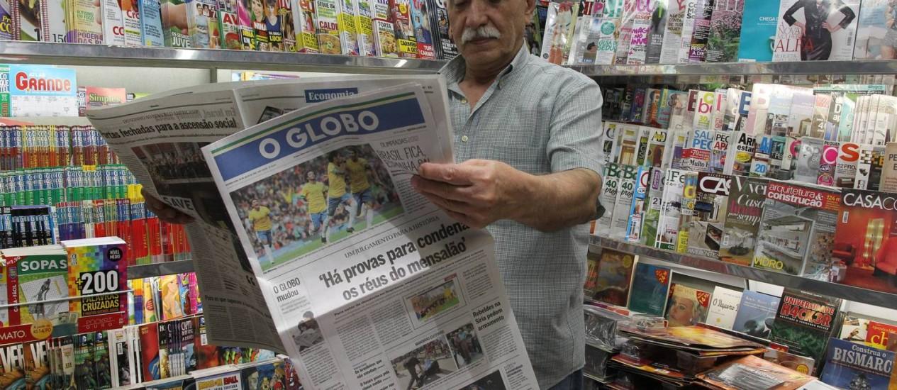 Há 45 anos vendendo jornais no Humaitá, Settimio Aloise mostra a capa do GLOBO e diz que aprovou Foto: Domingos Peixoto / O Globo