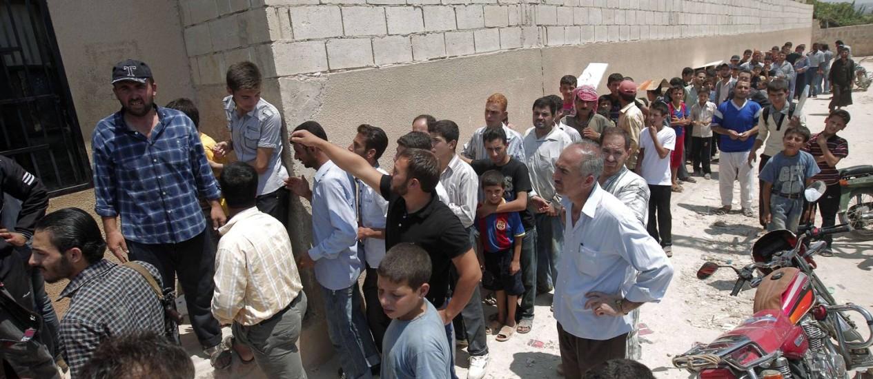 Sírios fazem fila para comprar pão em uma padaria na cidade de Aldana, perto de Aleppo: pelo menos 15 pessoas estão desabrigadas, sem conseguir fugir da cidade Foto: AHMAD GHARABLI / AFP