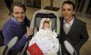 O bebê Tobias Grinblat Dermgerd entre seus dois pais, Alejandro Grinblat e Gustavo Dermgerd, em frente a um cartório em Buenos Aires, na Argentina Foto: JUAN MABROMATA/AFP