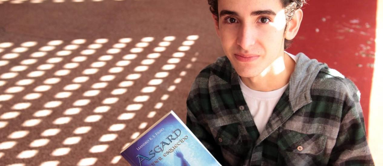 """Leandro Rodrigues Sales Filho, de 16 anos, e seu livro """"Asgard"""" Foto: Eliária Andrade"""