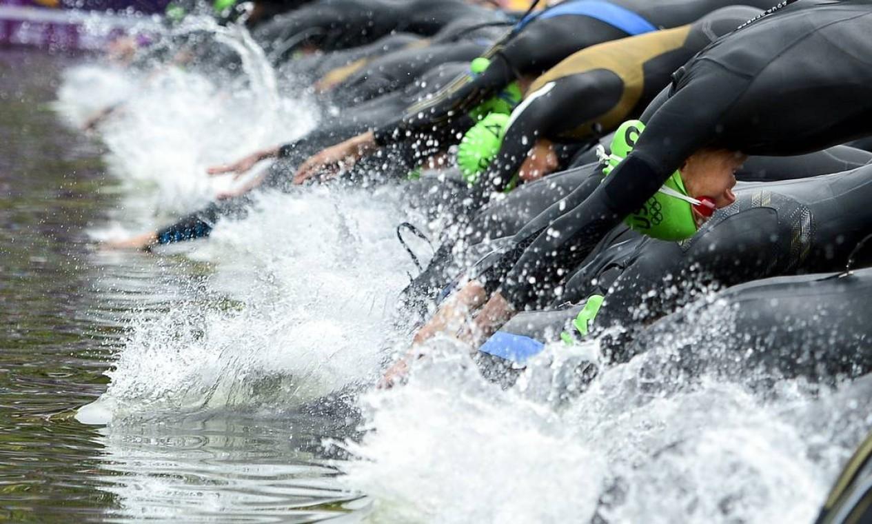 Atletas mergulham para a fase de natação do triatlo Foto: AFP Photo