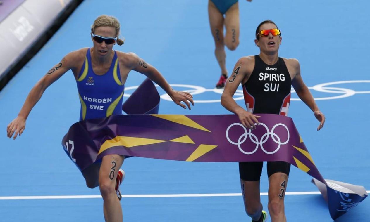 Após a longa competição no triatlo, a medalhista de ouro Nicola Spirig (Suíça) e a de prata, Lisa Norden (Suécia) chegaram praticamente juntas na final. Um pouco atrás está a medalhista de bronze, Erin Densham (Austrália) Foto: AP Photo