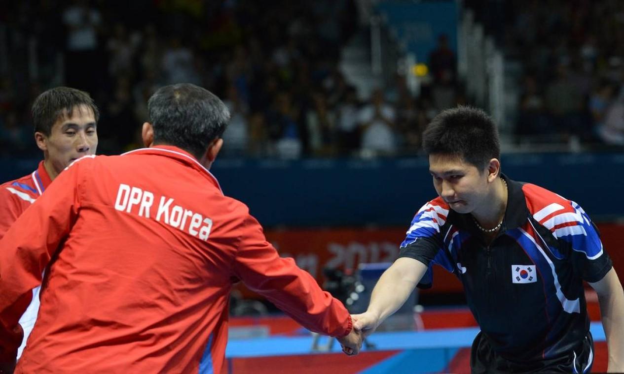 Ryu Seungmin, da Coreia do Sul, aperta a mão do técnico da Coreia do Norte após derrotar Kim Hyok Bong no tênis de mesa Foto: AFP Photo