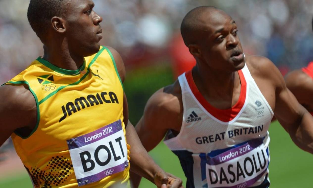 Usain Bolt olha para o adversário durante a prova classificatória dos 100m rasos Foto: AFP Photo