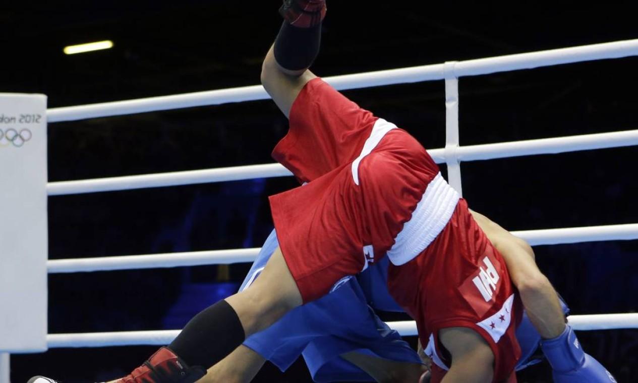 Mark Barriga, das Filipinas, e Birzhan Zhakypov, do Cazaquistão, caem durante luta de boxe no peso mosca. Zhakypov ganhou por pontos Foto: AP Photo