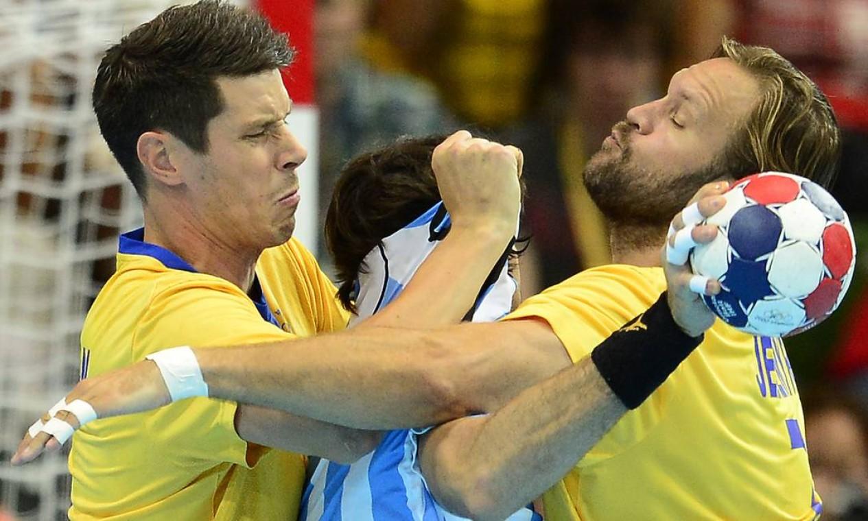 Jogadores suecos agarram atleta argentino para impedir jogada no handebol masculino Foto: AFP Photo