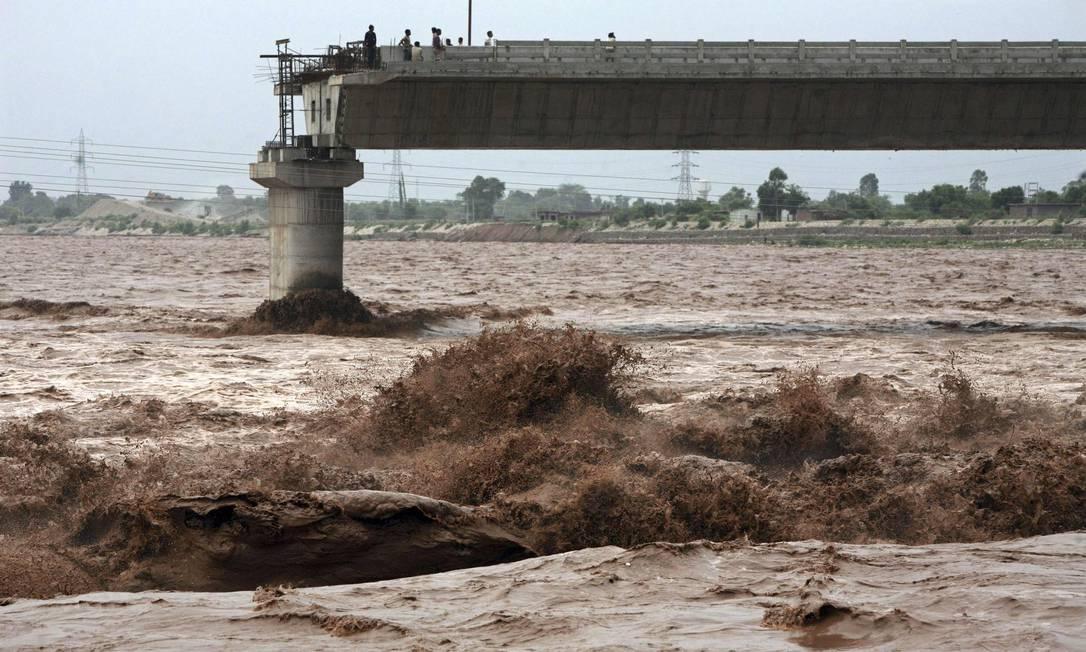Pessoas observam a correnteza no rio Tawi, afetado por uma enchente, em cima de uma ponte inacabada, na região de Jammu, na Índia. Cerca de 22 pessoas ficaram presas nas inundações MUKESH GUPTA / REUTERS