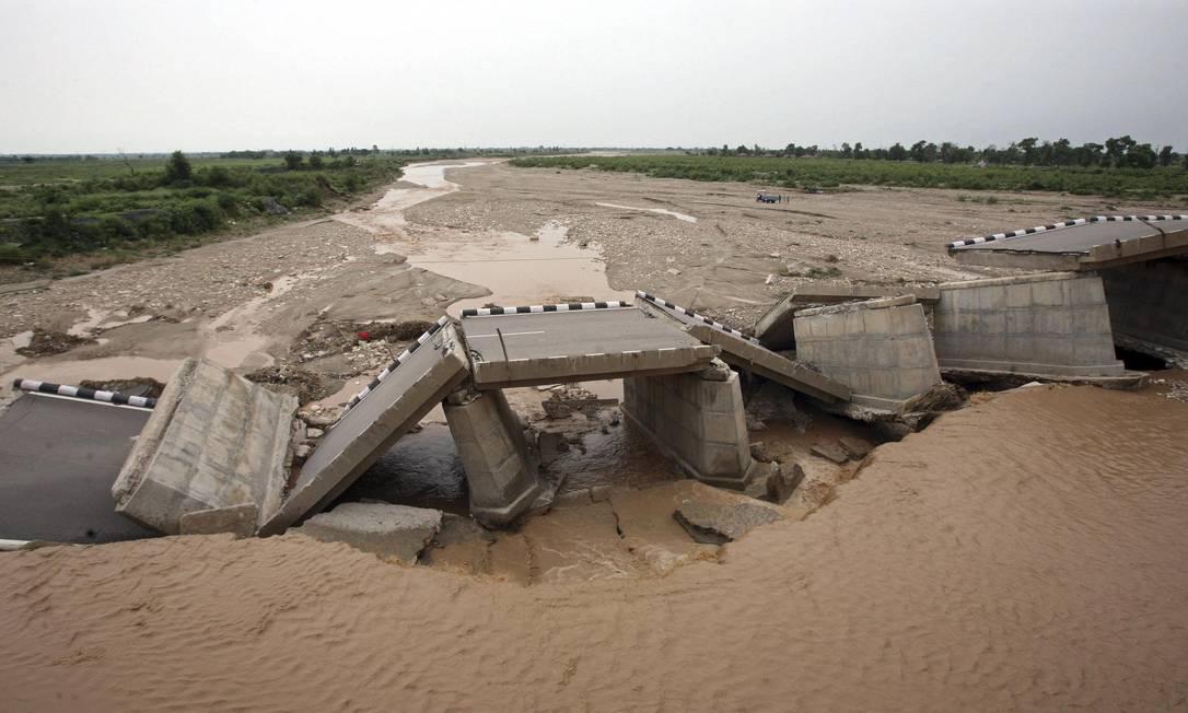 Uma ponte construída sobre o rio Tawi é derrubada pela enchente na região de Jammu, na Índia, este sábado (4) MUKESH GUPTA / REUTERS