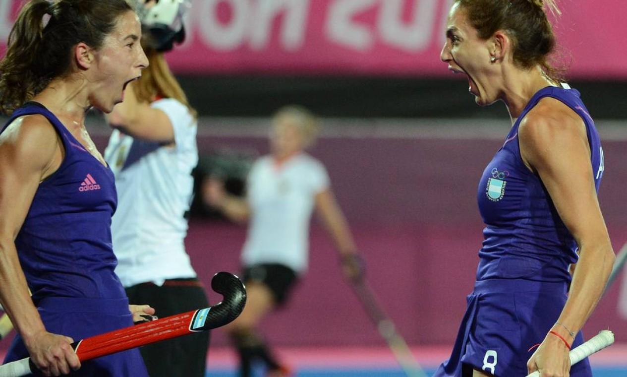 As argentinas Rosario Luchetti e Luciana Aymar comemoram um gol sobre a Alemanha no hóquei Foto: INDRANIL MUKHERJEE / AFP