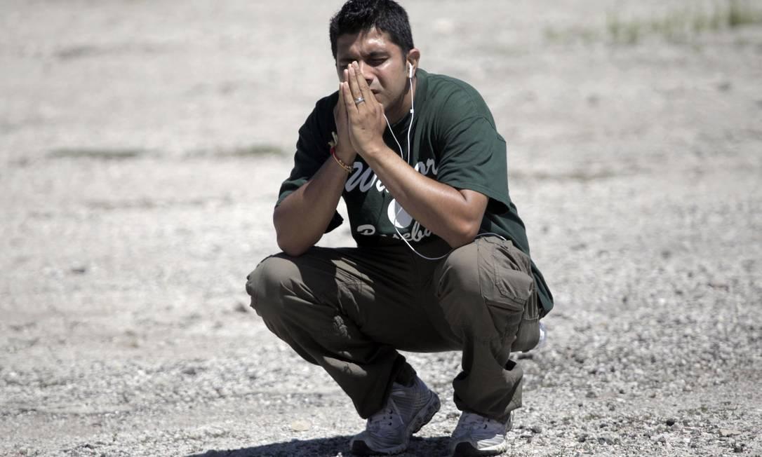 Familiar de uma das supostas vítimas do ataque reza no estacionamento próximo ao templo Foto: Mike De Sisti / AP Photo/Milwaukee Journal-Sentinel