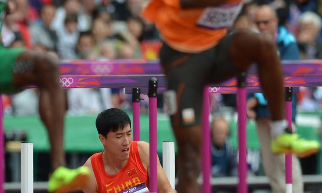 Liu Xiang caído no chão após atingir o primeiro obstáculo nos 100 metros com barreira Foto: Eric Fefferberg / AFP Photo