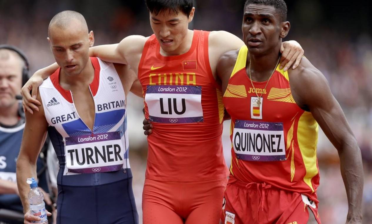 Após o fim da prova, Turner e Quiñonez ajudam Liu a sair da pista Foto: Anja Niedringhaus / AP Photo