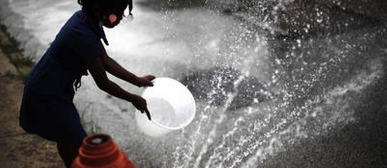 Menina enche balde em hidrante na Filadélfia: calor do mês passado foi maior do que o de 1936 Foto: Matt Rourke/AP/18-7-2012