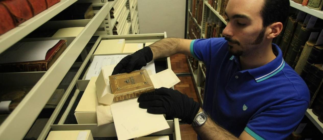 O bibliotecário Marcio Miquelino retira da caixa o missal que pertenceu à imperatriz Tereza Cristina Foto: Guilherme Leporace / Agência O Globo