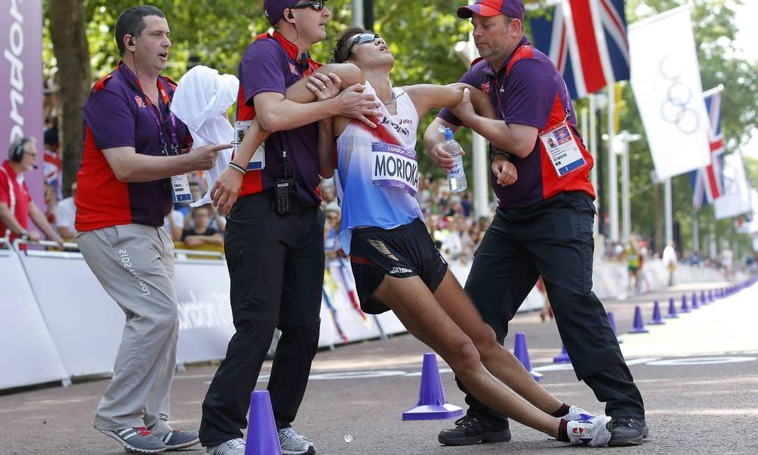 O japonês Koichiro Morioka é ajudado após cruzar a linha de chegada na marcha atlética Foto: Reuters