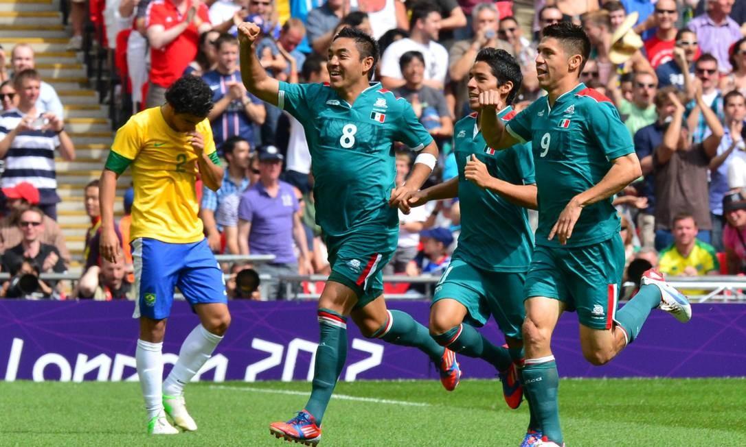 Jogadores do México comemoram o gol enquanto o lateral Rafael lamenta - o camisa 2 do Brasil errou o passe no início da jogada Foto: LUIS ACOSTA / AFP