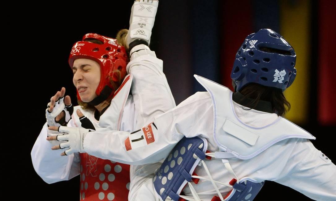 Natalia Falavigna leva um golpe da sul-coreana Lee In Jong. A brasileira foi derrotada em sua primeira luta no torneio feminino de taekwondo Foto: TOSHIFUMI KITAMURA / AFP